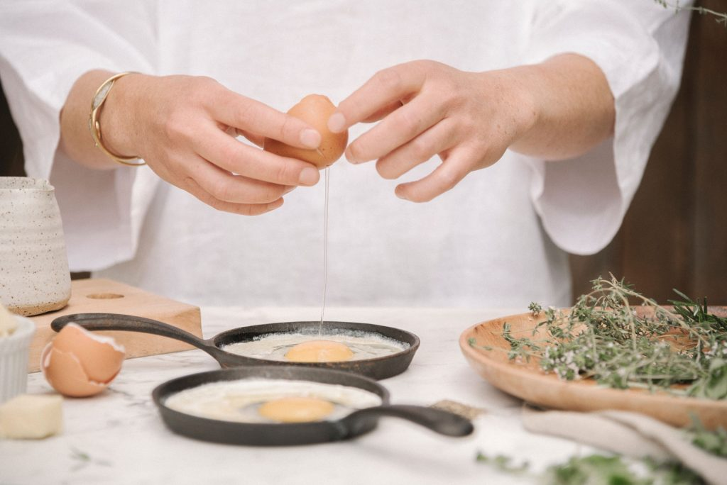 Chef cracking egg into cast iron pan | Featured image for restaurant suppliers home page.